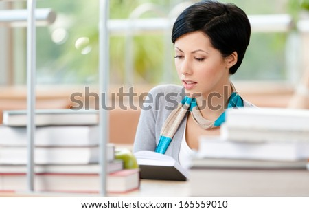 Woman surrounded with piles of books reads sitting at the table at the library. Information concept - stock photo
