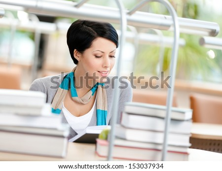 Woman surrounded with piles of books reads sitting at the table at the library. Knowledge concept - stock photo
