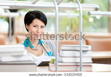 Woman surrounded with piles of books reads sitting at the table at the library. Learning concept