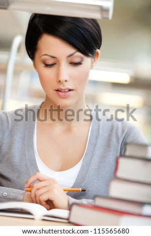Woman surrounded with piles of books reads sitting at the table at the reading hall. Information overload - stock photo