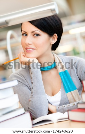 Woman surrounded with piles of books reads sitting at the table at the reading hall. Information concept - stock photo