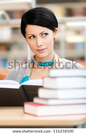 Woman surrounded with piles of books reads sitting at the table at the reading hall. Learning process