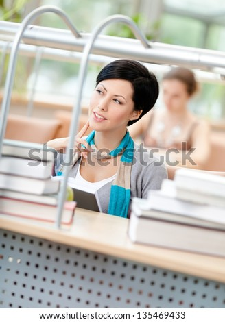 Woman surrounded with piles of books reads sitting at the table at the reading hall. Process of education