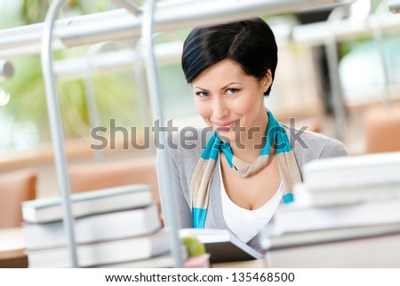 Woman surrounded with piles of books reads sitting at the table at the reading hall. Studying process - stock photo