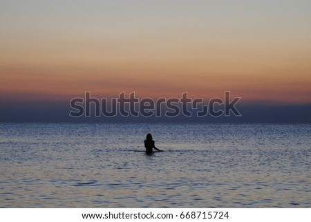 Woman swimming during the sunset