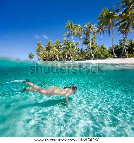 Woman swimming in a clear tropical waters in front of exotic island