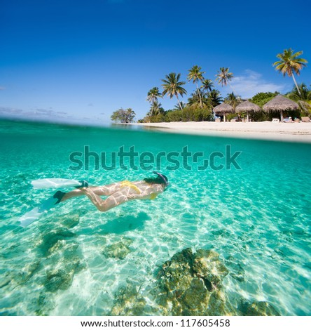 Woman swimming in a tropical lagoon in front of exotic island