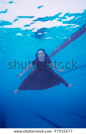 Woman swimming in the pool in  clothes - underwater shoot