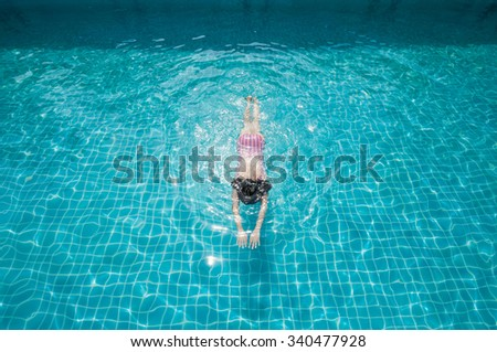 Woman swimming on a blue water pool.  - stock photo