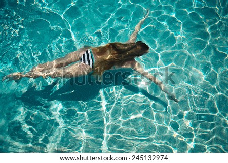Woman swimming on a blue water pool. Summertime - stock photo