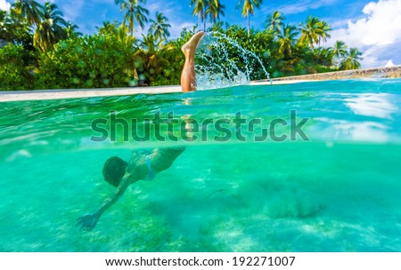 Woman swimming underwater, diving in turquoise transparent sea, wonderful tropical nature, summer adventure and tourism concept