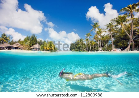 Woman swimming underwater in clear tropical waters in front of exotic island - stock photo