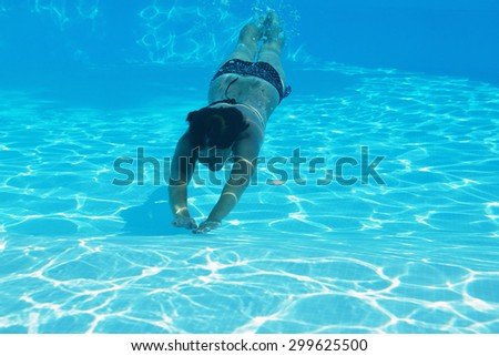woman swimming underwater in pool