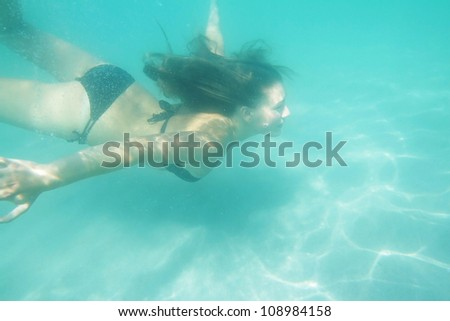 woman swimming underwater in sea - stock photo