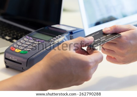 woman swipes her credit card to make the payment - stock photo