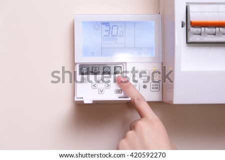 Woman switching a digital thermostat - stock photo