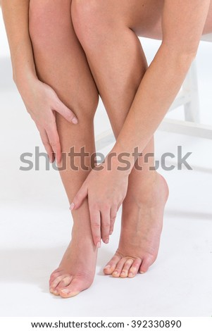Woman tacking care of her  legs sitting on white background