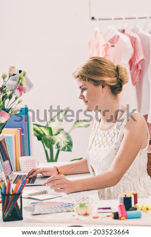 Woman tailor working on the laptop in her workshop, side view - stock photo