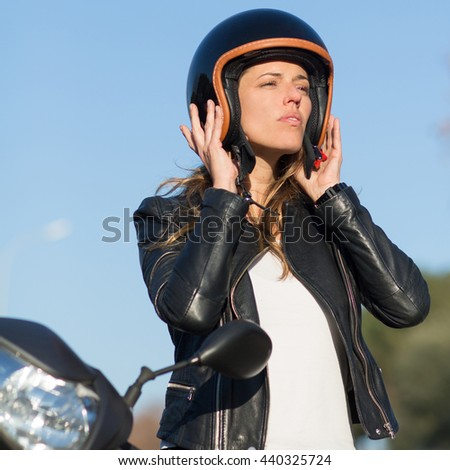 Woman takes off helmet on scooter - stock photo