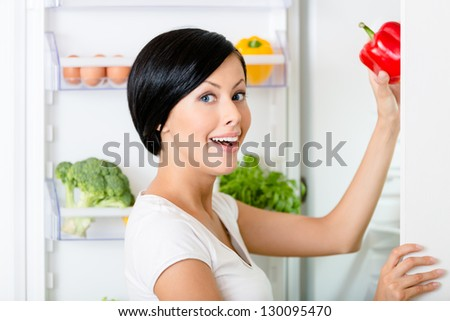Woman takes red pepper from the opened fridge full of vegetables and fruit. Concept of healthy and dieting food