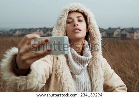 woman takes selfies in fields behind country town - stock photo