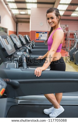 Woman taking a break on the treadmill after exercising - stock photo