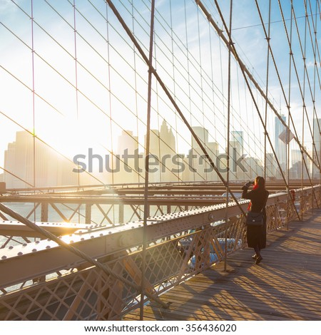 Woman taking a photo from Brooklyn bridge. New York City Manhattan downtown skyline in sunset with skyscrapers illuminated over East River panorama as seen from Brooklyn bridge. - stock photo