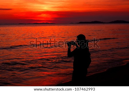 Woman taking a photograph silhouette the sea sunset