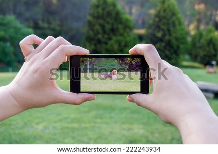 Woman taking a picture with a phone in case your dog is lost - stock photo