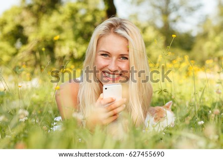 Woman taking a selfie in a summer park