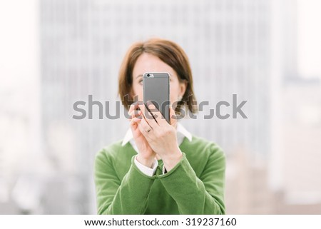 Woman taking a selfie with a smartphone in an urban business background