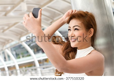 woman taking a selfie with her smartphone