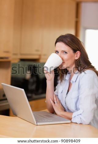 Woman taking a sip of coffee next to her laptop - stock photo