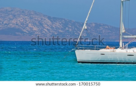woman taking a sunbath on a sailing boat - stock photo