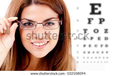 Woman taking an eye vision test and wearing glasses - stock photo