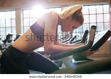 Woman taking break during cycling workout in gym. Female on gym bike doing cardio exercise. - stock photo