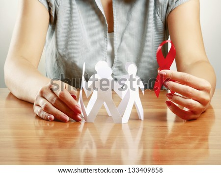 woman taking care about paper people and aids, isolated on grey - stock photo