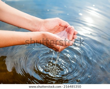Woman taking clear water at a lake by hands - stock photo
