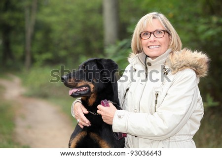 Woman taking dog for a walk - stock photo