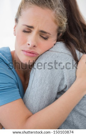 Woman taking her sad friend in her arms while closing eyes