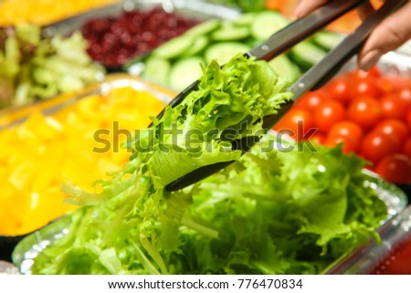 Woman taking ingredient for salad, close up