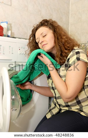 woman taking linen from washing machine