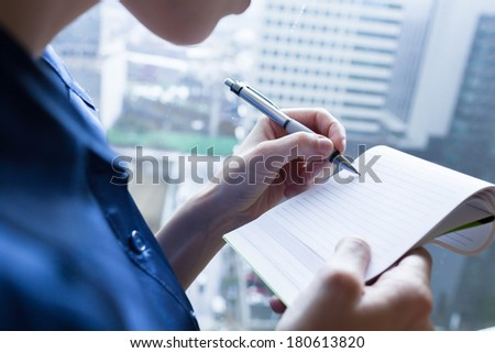 Woman taking notes during business meeting in the office. - stock photo
