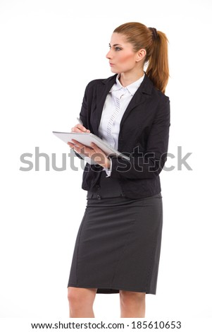 Woman taking notes. Elegance woman in black suit looking away and writing. Three quarter length studio shot isolated on white.