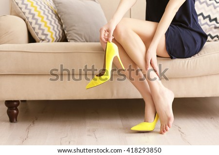 Woman taking off yellow high heels shoes. - stock photo