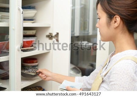 Woman taking out dishware of the cupboard