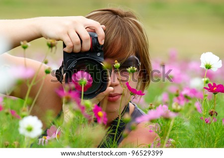 Woman taking photo in a field of Cosmos Flowers - stock photo