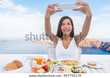 Woman taking photo of breakfast using mobile cell smart phone app. Girl taking pictures of food on luxury travel vacation for social media. Beautiful female in resort in Santorini, Greece, Europe. - stock photo
