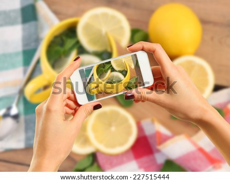 Woman taking photo of tea with lemon with smartphone - stock photo
