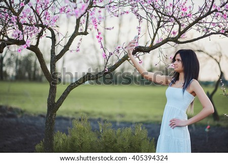 Woman taking photo tree blossoms with mobile phone